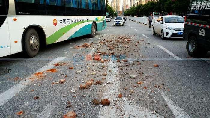 """遗撒30多米碎砖石占一排行车道 后面车辆""""行路难"""""""