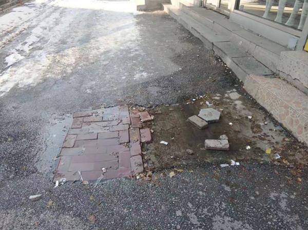 新华大街这地儿漏水 顺着人行道淌了老远了