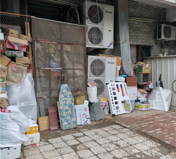"""楼下堆杂物引担心 居民建议放到小区里的""""可回收物品""""箱"""