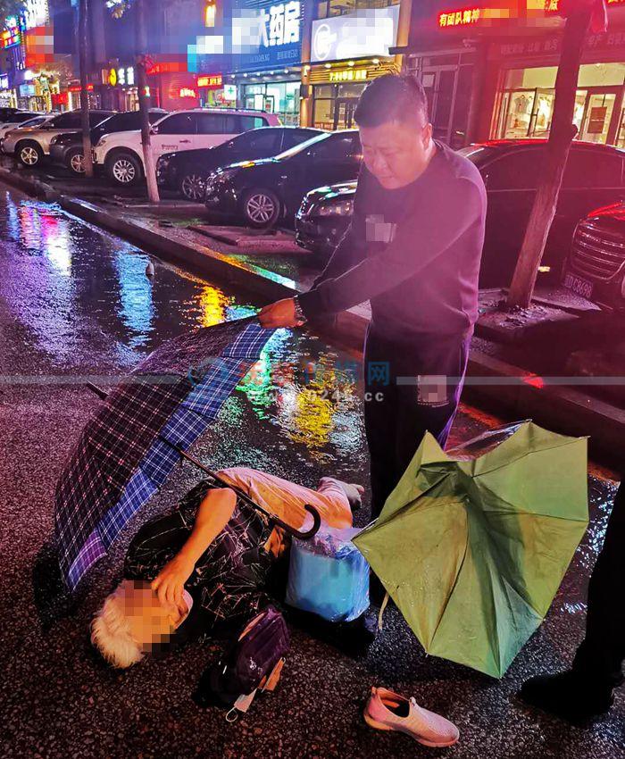 风雨中老人被撞倒地 俩路过男子撑伞守护