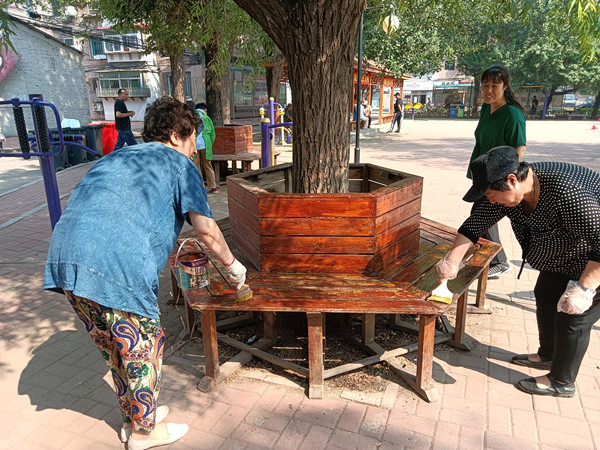 志愿者粉刷社区休闲设施 让家园更美丽